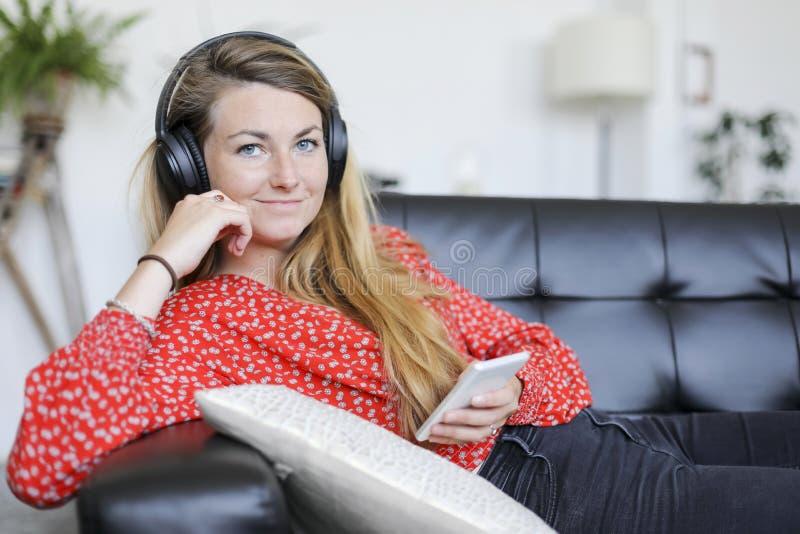 Gelukkige vrouw die aan muziek luisteren die hoofdtelefoons dragen die nok bekijken royalty-vrije stock afbeeldingen
