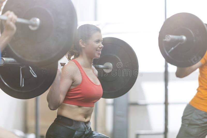 Gelukkige vrouw die barbell in crossfitgymnastiek opheffen stock foto's