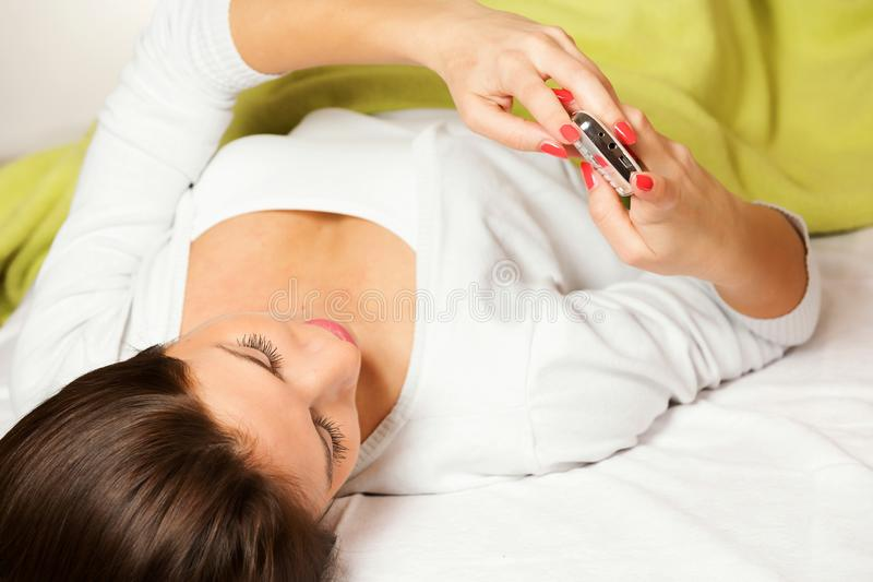Gelukkige vrouw die bij bed glimlachen liggen, die een tekstbericht lezen royalty-vrije stock afbeeldingen