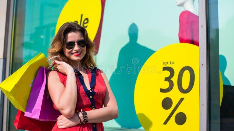 Gelukkige vrouw die bij een openluchtwandelgalerij winkelen. stock foto