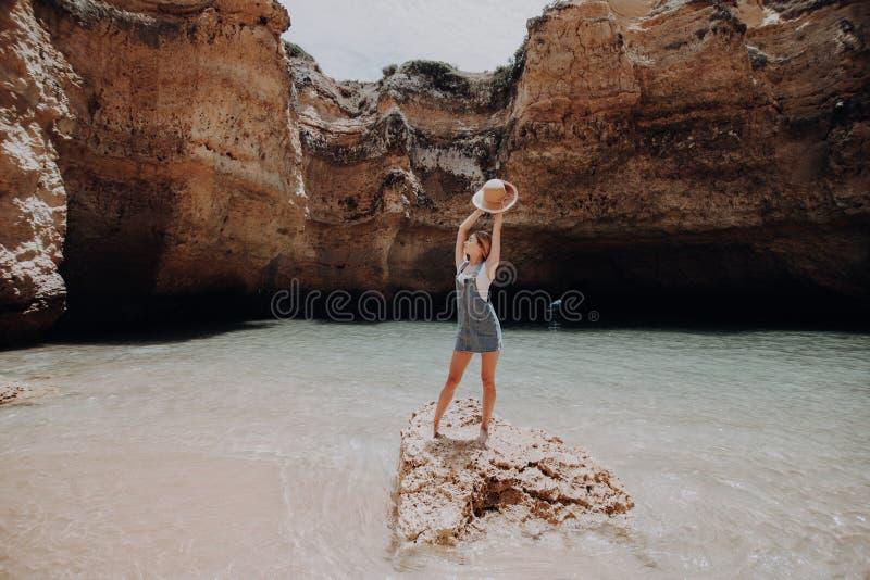 Gelukkige vrouw die bij het rotsstrand genieten van Het concept van de zomervakanties royalty-vrije stock foto's