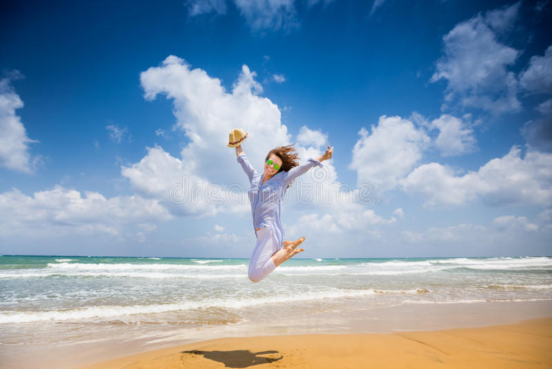 Gelukkige vrouw die bij het strand springen stock afbeeldingen