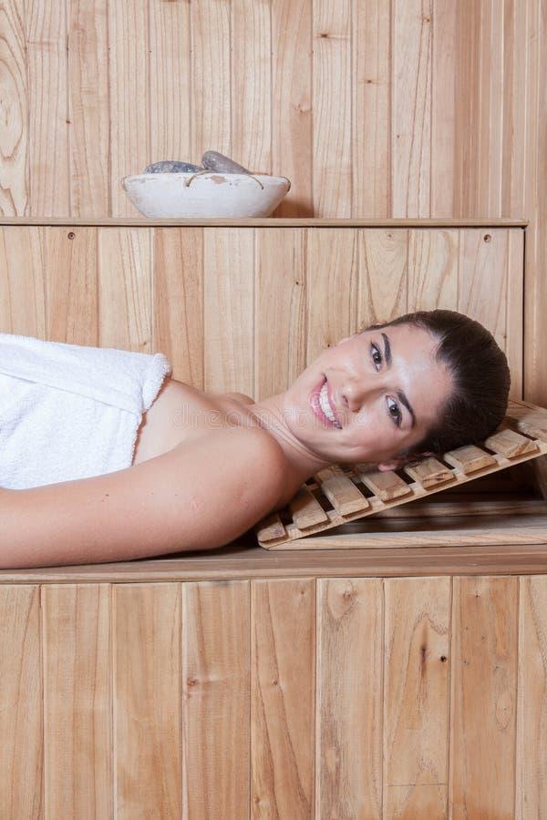Gelukkige vrouw die binnen de sauna liggen royalty-vrije stock afbeelding