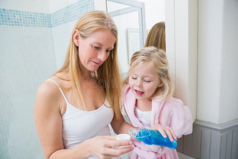 Gelukkige vrouw die blauwe mondspoeling met dochter gieten royalty-vrije stock afbeeldingen