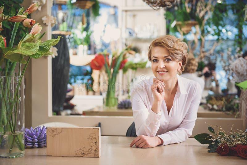 Gelukkige vrouw die in bloemwinkel werken royalty-vrije stock foto's