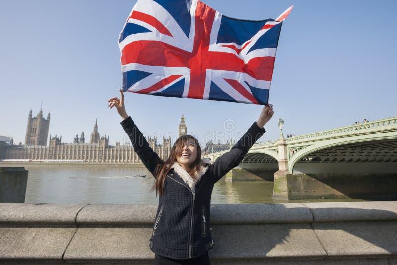 Gelukkige vrouw die Britse vlag houden terwijl status tegen Big Ben in Londen, Engeland, het UK royalty-vrije stock foto's
