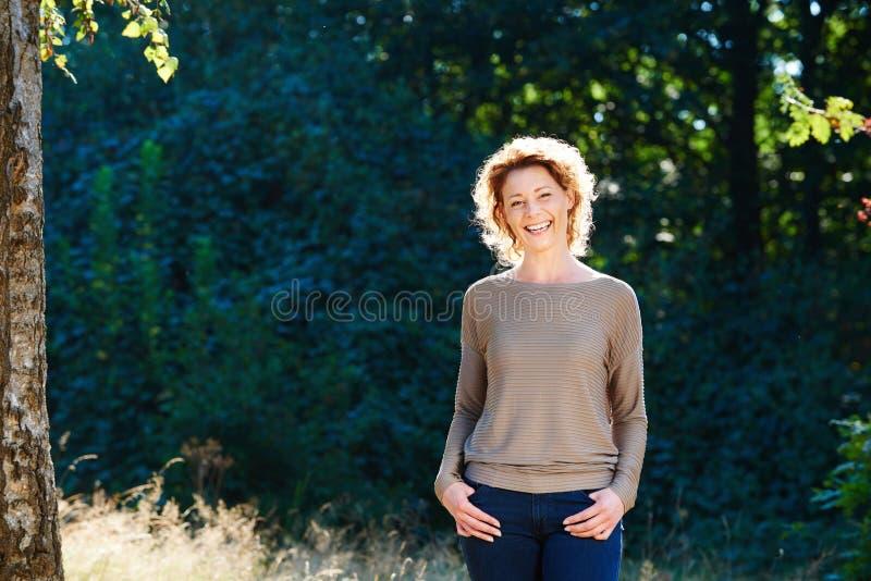 Gelukkige vrouw die buiten in aard lachen royalty-vrije stock afbeelding