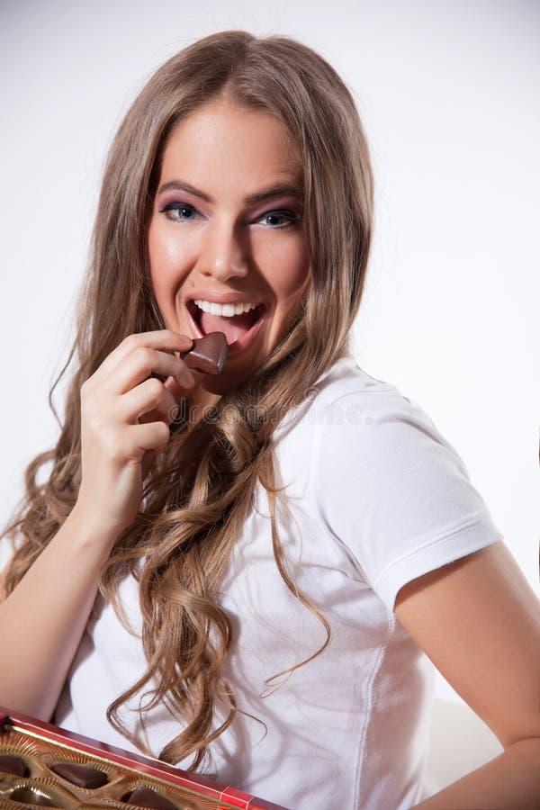 Gelukkige vrouw die chocolade eten stock foto