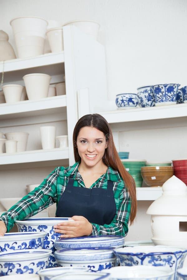 Gelukkige vrouw die de camera bekijken die in een keramiekwinkel werken stock fotografie