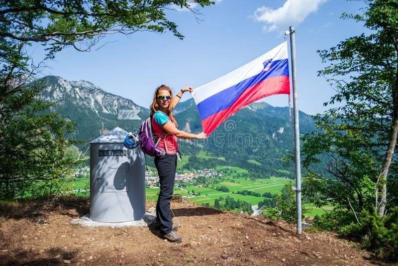Gelukkige vrouw die de Sloveense vlag na het beëindigen van beklimmen tonen via ferrataroute op de Grancisce-heuvel, boven Mojstr stock afbeelding