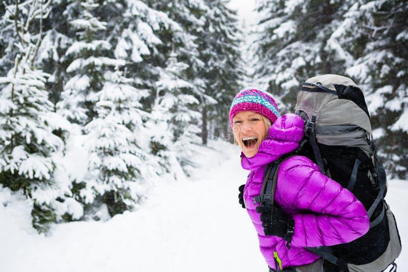 Gelukkige vrouw die in de winterbos lopen met rugzak stock fotografie