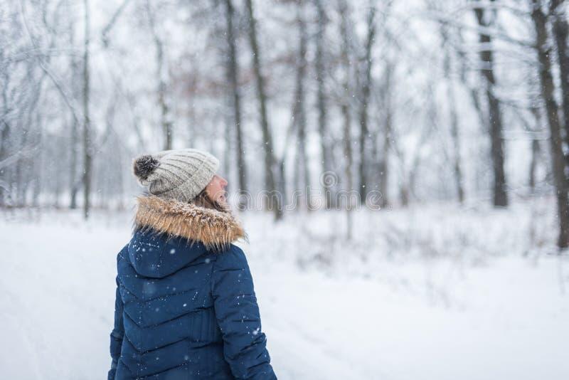 gelukkige vrouw die in de winterhout lopen die omhoog sneeuw het vallen bekijken stock afbeelding