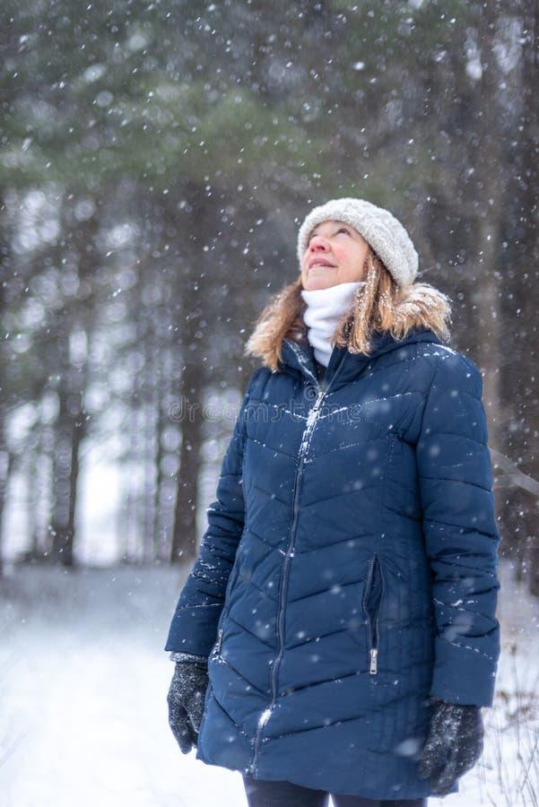 gelukkige vrouw die in de winterhout omhoog sneeuw het vallen bekijken stock foto
