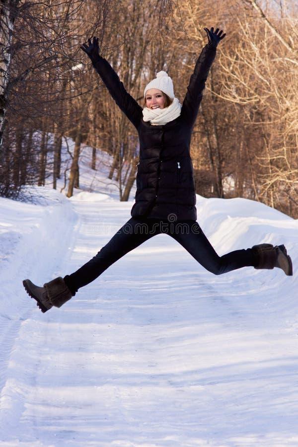 Gelukkige vrouw die in de winterjasje in openlucht springen. stock fotografie