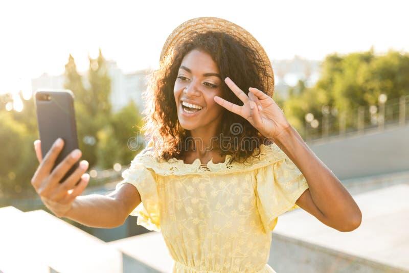 Gelukkige vrouw die in de zomerkleding bij de stad lopen, die mobiele telefoon houden stock foto