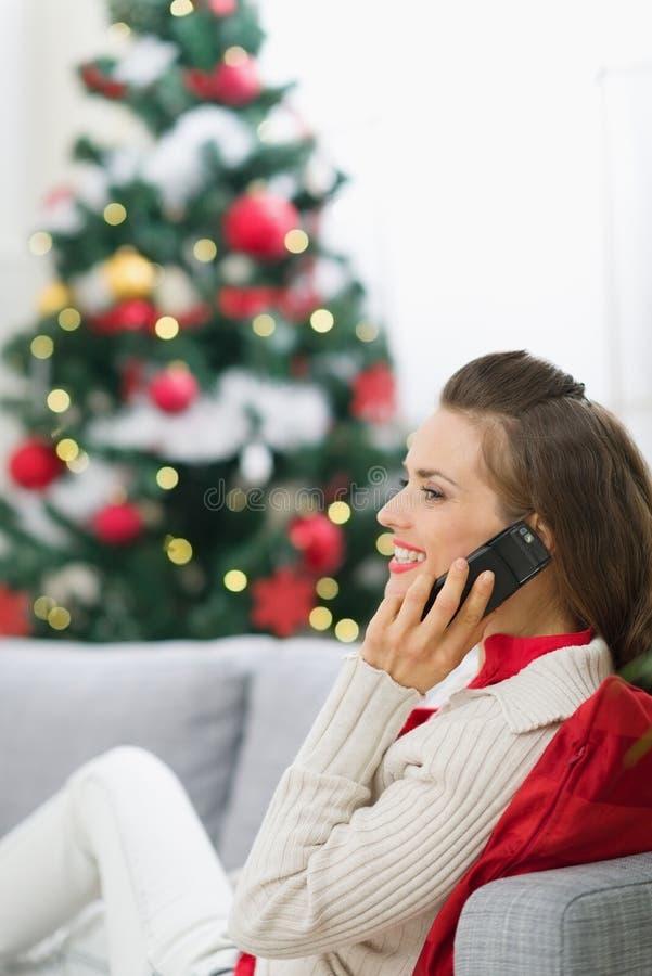 Gelukkige vrouw die dichtbij Kerstboom telefoongesprek maakt stock afbeeldingen