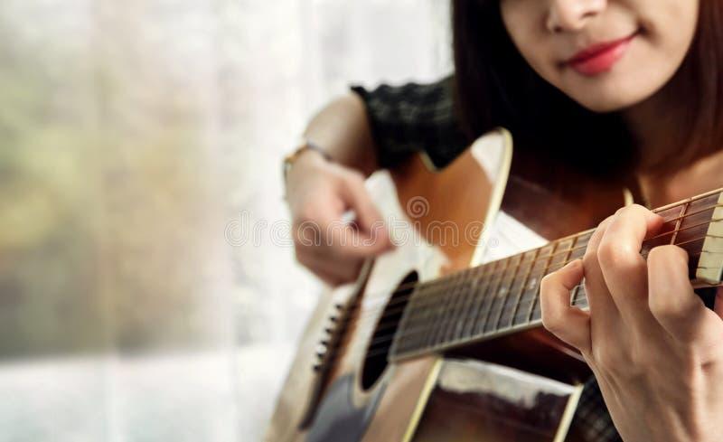 Gelukkige Vrouw die een Akoestische Gitaar spelen binnenshuis, Ontspanning en stock afbeelding