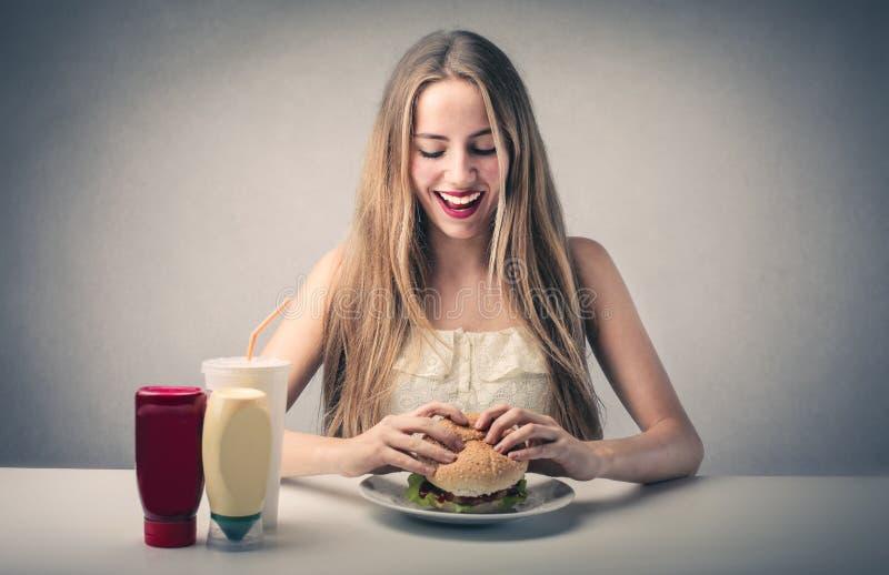 Gelukkige vrouw die een hamburger eten royalty-vrije stock afbeelding