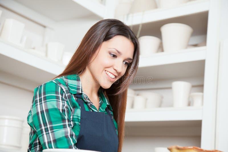 Gelukkige vrouw die in een keramiekwinkel werken royalty-vrije stock fotografie