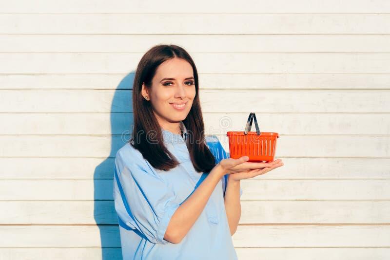 Gelukkige Vrouw die een Kleine Rode het Winkelen Mand houden royalty-vrije stock foto's