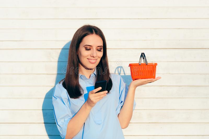 Gelukkige Vrouw die een Kleine Rode het Winkelen Mand houden royalty-vrije stock afbeelding