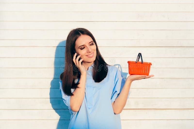 Gelukkige Vrouw die een Kleine Rode het Winkelen Mand houden stock foto's