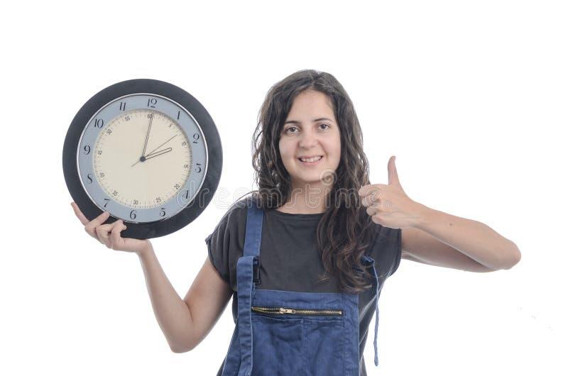 Gelukkige vrouw die een klok over witte achtergrond houden stock afbeelding