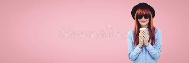 Gelukkige vrouw die een koffie houden tegen breed leeg roze stock afbeelding