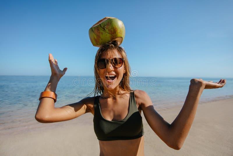 Gelukkige vrouw die een kokosnoot op haar hoofd in evenwicht brengen bij het strand stock afbeeldingen