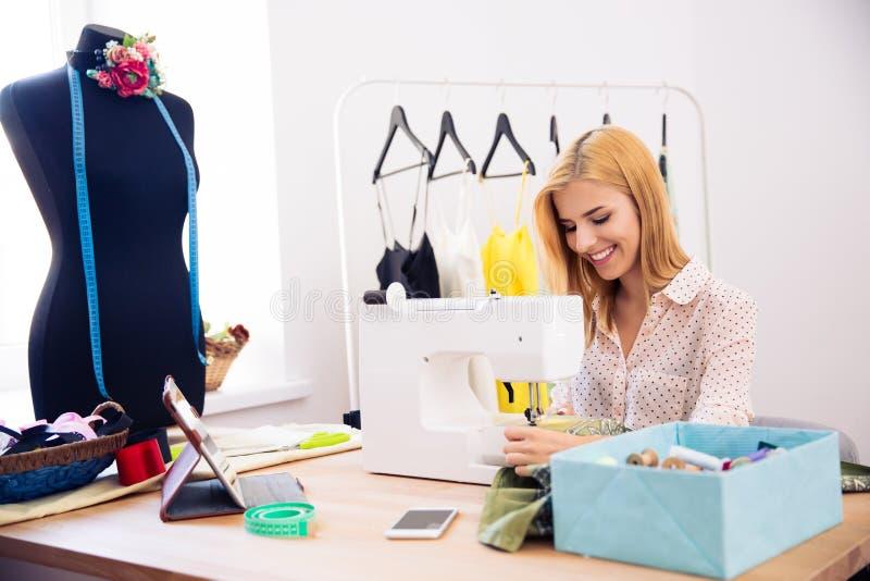 Gelukkige vrouw die een naaimachine met behulp van royalty-vrije stock foto