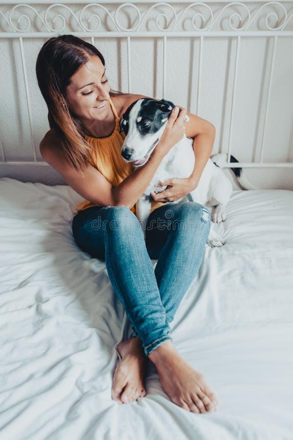 Gelukkige vrouw die een puppy van Labrador in bed petting Het puppy van Labrador is in haar wapens royalty-vrije stock foto