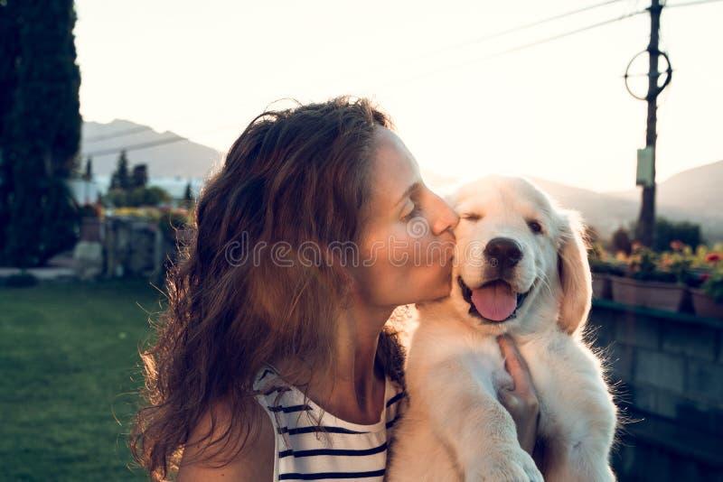 Gelukkige vrouw die een puppyhond kussen bij zonsondergang royalty-vrije stock foto's