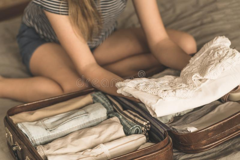 Gelukkige vrouw die een reis plannen die een koffer voorbereiden stock afbeeldingen