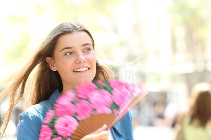 Gelukkige vrouw die een ventilator met behulp van die in de straat op de zomer lopen royalty-vrije stock foto