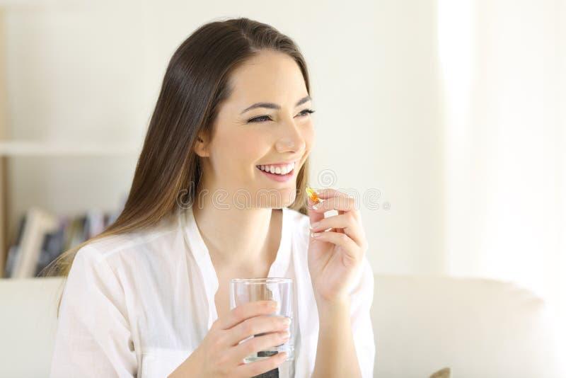 Gelukkige vrouw die een vitamine gele pil thuis nemen stock afbeelding