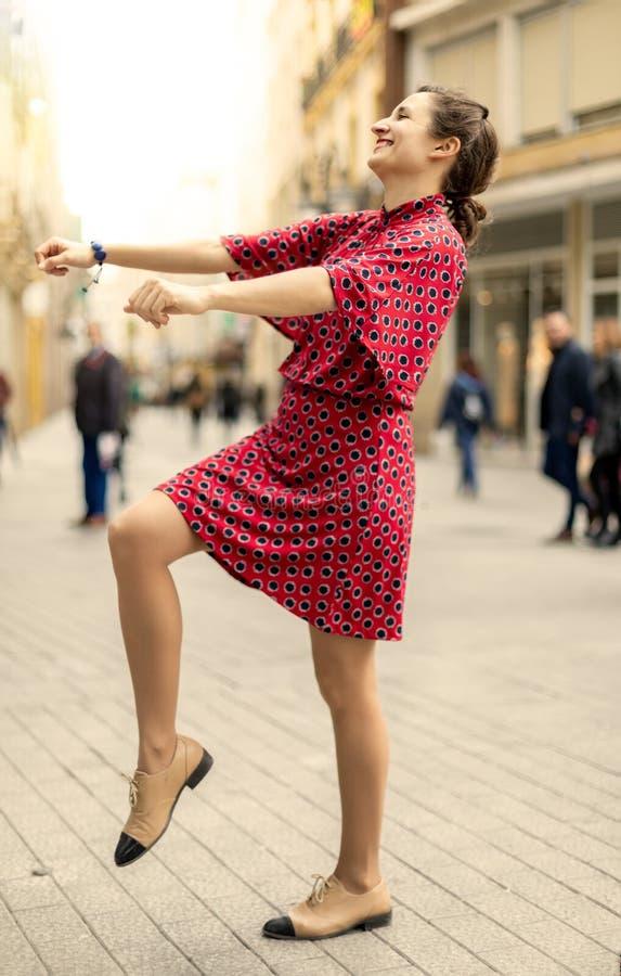 Gelukkige vrouw die en in de straat dansen glimlachen stock afbeeldingen
