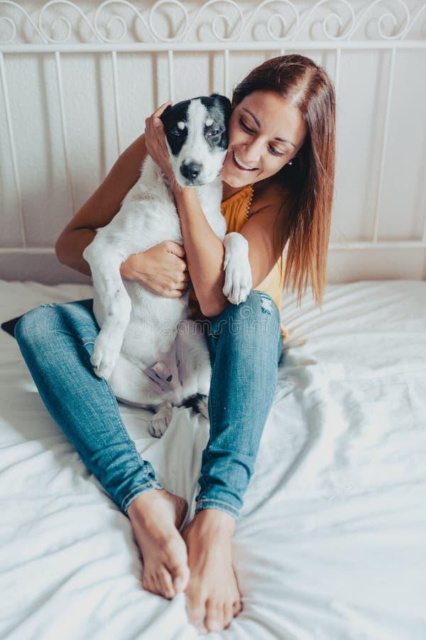Gelukkige vrouw die en een puppy van Labrador in bed koesteren behandelen Het puppy van Labrador is in haar wapens royalty-vrije stock foto's