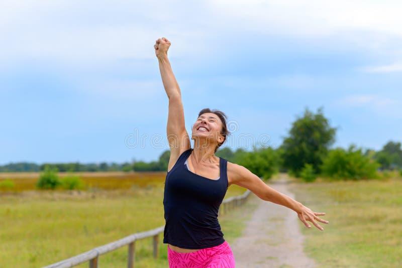 Gelukkige vrouw die en na het uitwerken van jogging toejuichen vieren royalty-vrije stock fotografie