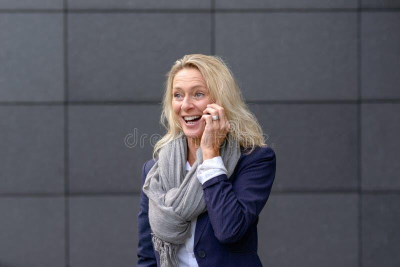 Gelukkige vrouw die en op mobiel haar lachen babbelen royalty-vrije stock foto's