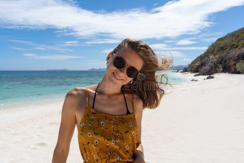 Gelukkige vrouw die en pret glimlachen hebben bij strand stock afbeelding