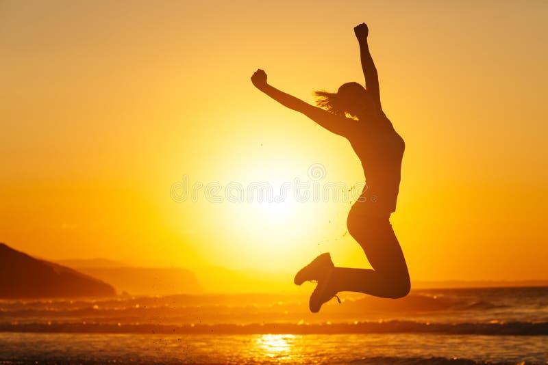 Gelukkige vrouw die en pret springen hebben bij het strand stock foto's