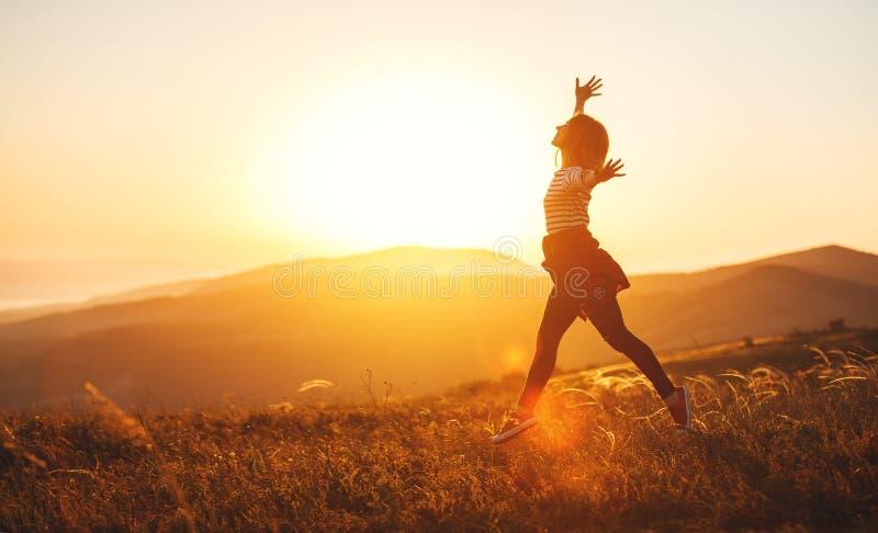 Gelukkige vrouw die en van het leven springen genieten bij zonsondergang in bergen royalty-vrije stock fotografie