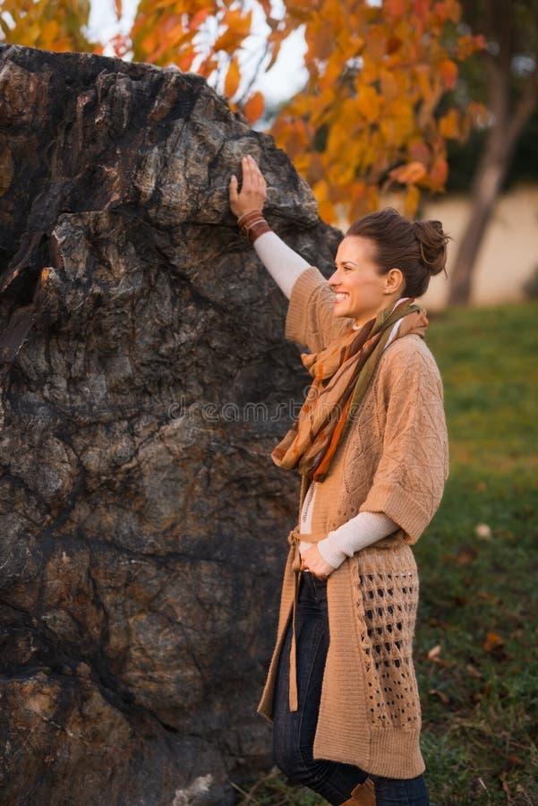 Gelukkige vrouw die in gebreide cardigan van avond in de herfstpark genieten royalty-vrije stock foto
