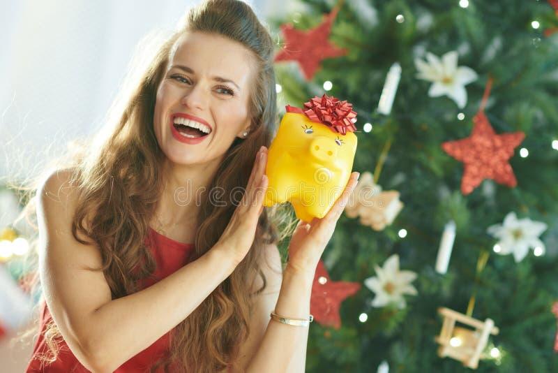 Gelukkige in vrouw die geel spaarvarken met rode boog schudden stock afbeelding