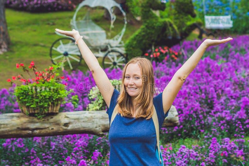 Gelukkige vrouw die geur van bloemen over de achtergrond van de de lentetuin genieten royalty-vrije stock afbeeldingen