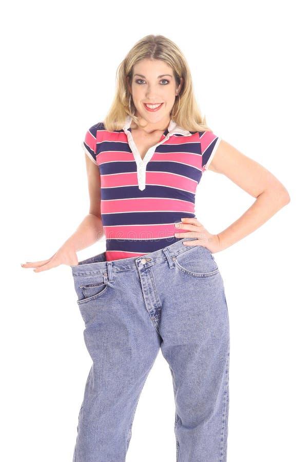 Gelukkige vrouw die gewichts met verlies pronkt royalty-vrije stock afbeeldingen