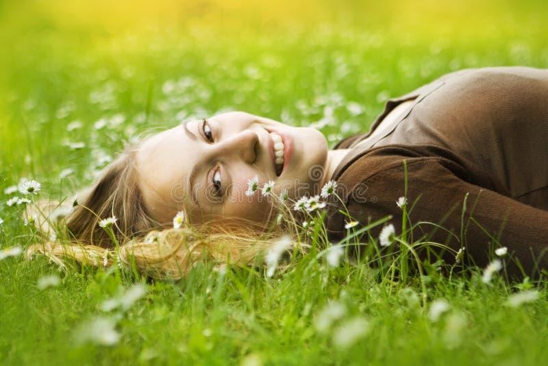 Gelukkige vrouw die in gras ligt stock afbeeldingen