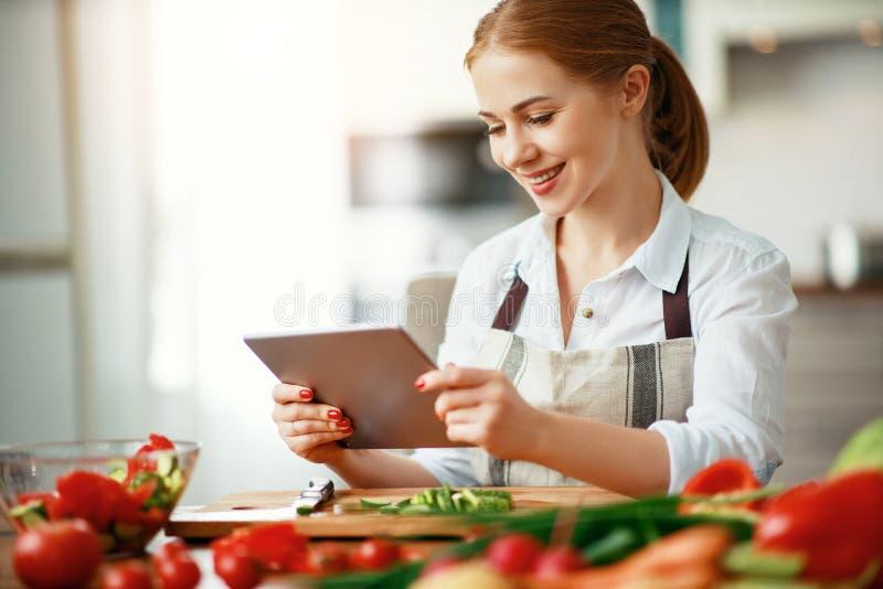 Gelukkige vrouw die groenten in keuken op voorschrift met tablet voorbereiden stock afbeelding