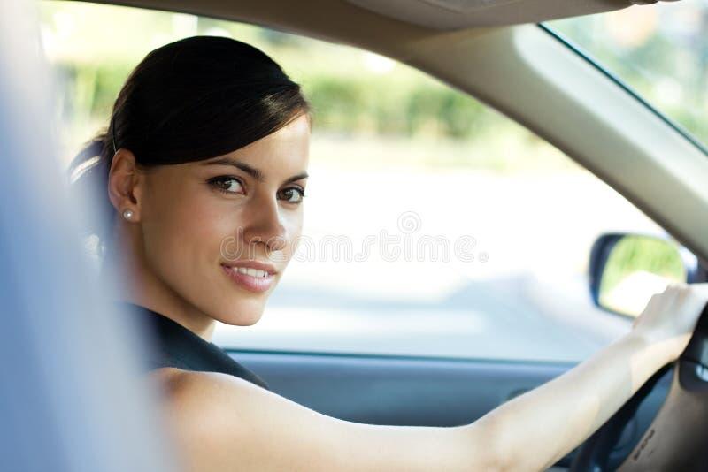 Gelukkige vrouw die haar auto drijft stock afbeelding