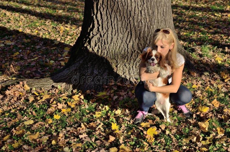 Gelukkige vrouw die haar hond kussen stock fotografie